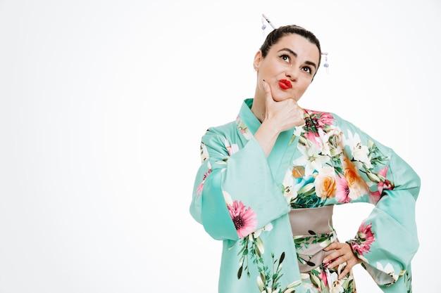 Frau im traditionellen japanischen kimono, die mit nachdenklichem ausdruck aufschaut und versucht, eine wahl zu treffen, die auf weiß denkt