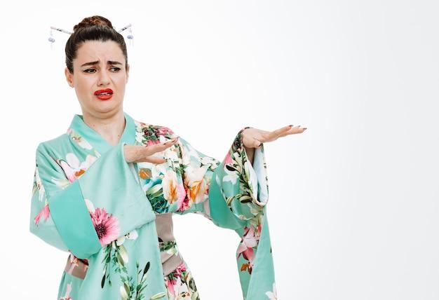 Frau im traditionellen japanischen kimono, die mit staubigem ausdruck beiseite schaut und verteidigungsgeste mit den händen auf weiß macht