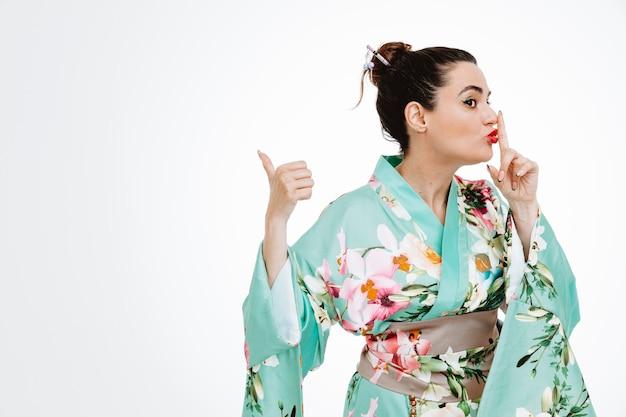Frau im traditionellen japanischen kimono, die selbstbewusst aussieht und stillegeste mit dem finger auf den lippen macht, die mit dem daumen zur seite auf weiß zeigt