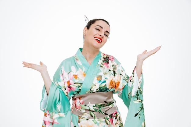 Frau im traditionellen japanischen kimono glücklich und erfreut, die arme breit lächelnd auf weiß zu heben