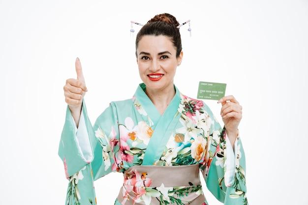 Frau im traditionellen japanischen kimono hält kreditkarte und zeigt daumen hoch auf weiß