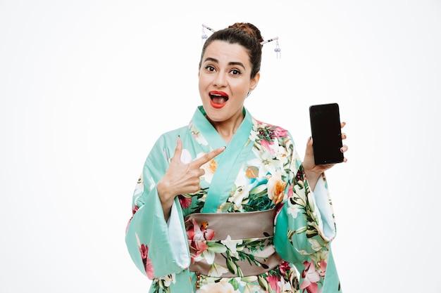 Frau im traditionellen japanischen kimono hält smartphone und zeigt mit dem zeigefinger darauf und lächelt selbstbewusst auf weiß