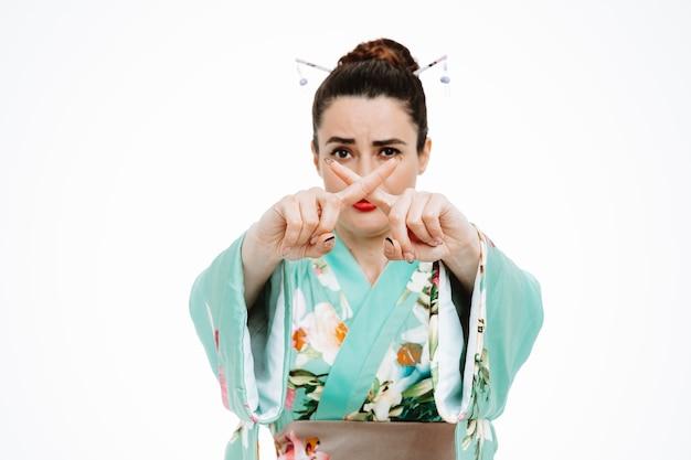Frau im traditionellen japanischen kimono mit ernstem gesicht, das stoppgeste macht, die zeigefinger auf weiß kreuzt