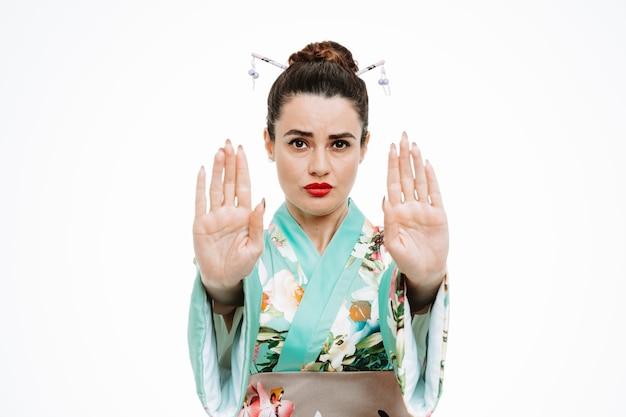 Frau im traditionellen japanischen kimono mit ernstem gesicht, das stoppgeste mit den händen auf weiß macht