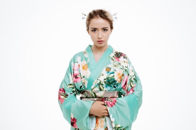 Frau im traditionellen japanischen kimono mit ernstem selbstbewusstem ausdruck auf weiß