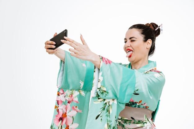Frau im traditionellen japanischen kimono mit smartphone macht selfie glücklich und fröhlich und streckt die zunge auf weiß aus