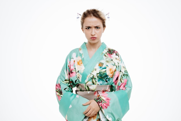 Frau im traditionellen japanischen kimono mit stirnrunzelndem wütendem gesicht auf weiß