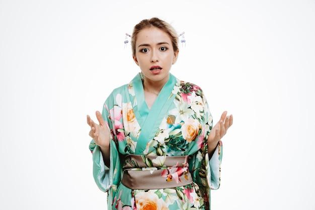 Frau im traditionellen japanischen kimono verwirrt und unzufrieden hebt die arme in empörung und unmut auf weiß