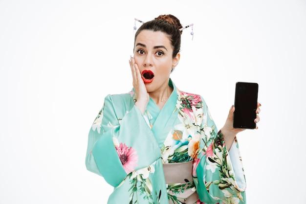 Frau im traditionellen japanischen kimono zeigt smartphone erstaunt und überrascht auf weiß