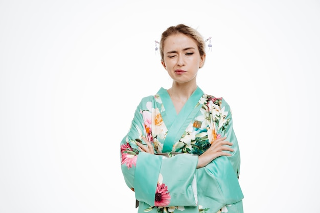 Frau im traditionellen japanischen kimono zwinkert und macht schiefen mund mit verschränkten armen auf weiß
