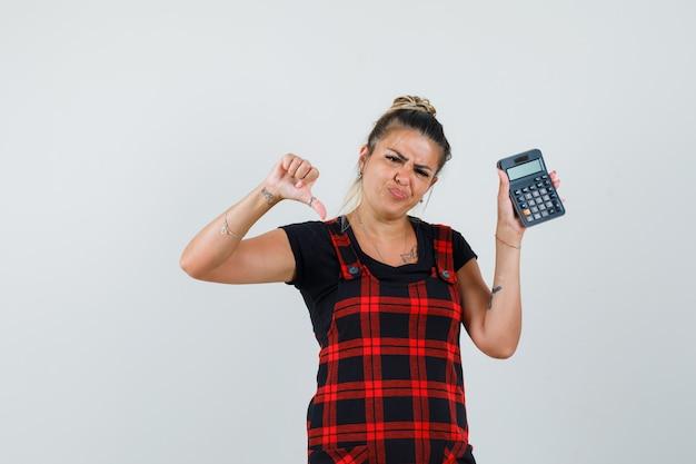Frau im trägerkleid hält taschenrechner, zeigt daumen nach unten und schaut enttäuscht, vorderansicht.