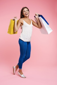Frau im trendigen frühling outfut hält bündel von einkaufstüten