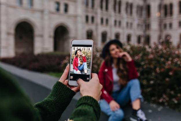 Frau im trendigen grünen pullover, der foto von ihrer schwester nimmt, die neben sitzt
