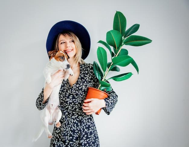 Frau im trendigen kleid mit pflanze in einem topf und hund