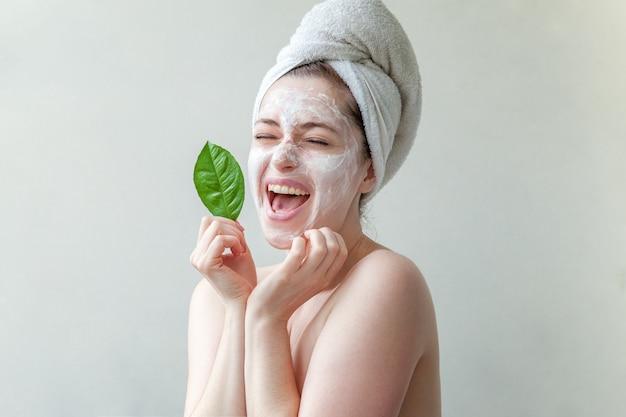 Frau im tuch auf kopf mit weißer ernährungsmaske oder creme auf gesicht und grünem blatt in der hand
