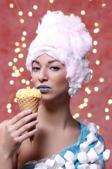 Frau im ungewöhnlichen kleid aus marshmallow und perücke aus zuckerwatte