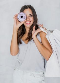 Frau im unterhemd mit einem donut und einkaufsnetzen