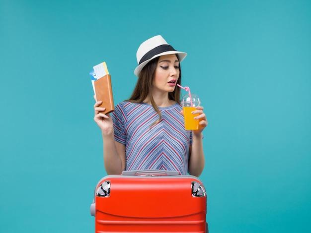 Frau im urlaub trinkt frischen saft und tickets auf blau
