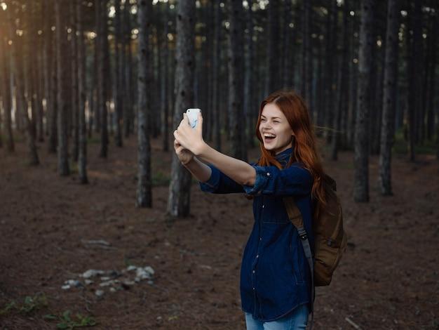 Frau im wald mit einem telefon in der hand reisen ferientourismus