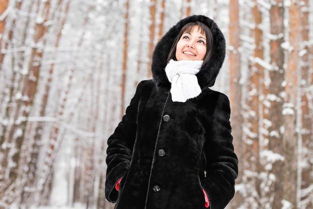 Frau im warmen mantel mit pelz im wald, kalter wintertag