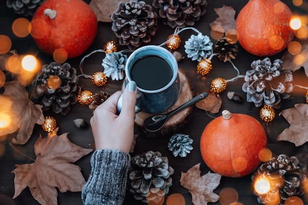 Frau im warmen pullover, der eine tasse heißen kaffee mit kürbissen, trockenen blättern und zapfen im hintergrund hält, herbstlebensstil, draufsicht