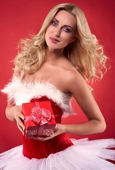 Frau im weihnachtskleid hält ein geschenk