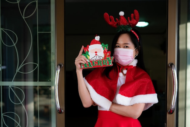 Frau im weihnachtsmannanzug mit tragender gesichtsmaske am weihnachtstag