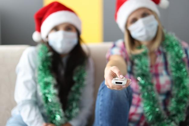 Frau im weihnachtsmannhut sitzen nebeneinander auf der couch.