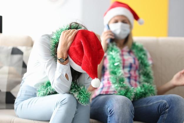 Frau im weihnachtsmannhut sitzt auf der couch mit gesenktem kopf neben frau in der medizinischen maske, die am telefon spricht