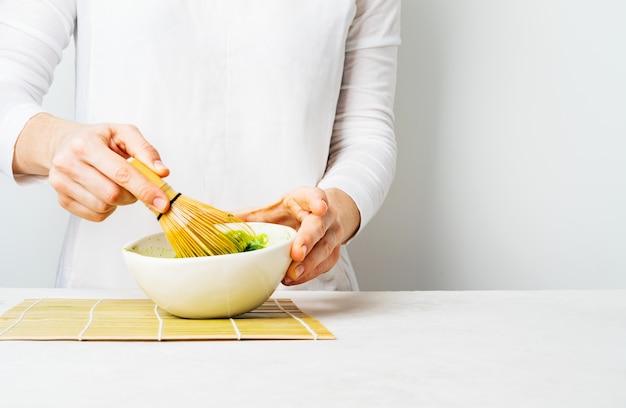 Frau im weiß bereiten japanischen grünen matcha-tee zu, indem sie ihn in einer schüssel peitschen