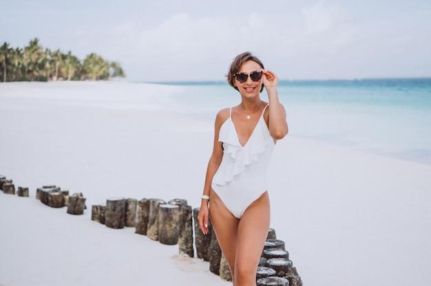 Frau im weißen badeanzug am meer