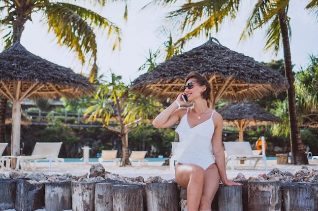Frau im weißen badeanzug durch den ozean unter verwendung des telefons