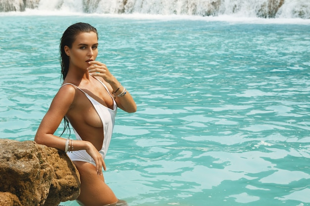 Frau im weißen badeanzug posiert auf dem felsen neben wasserfall