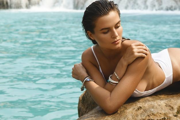 Frau im weißen badeanzug posiert auf dem felsen