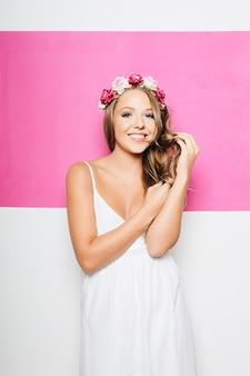 Frau im weißen baumwollkleid mit blumen beim haarlächeln