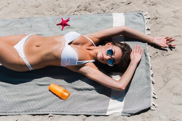 Frau im weißen bikini, der auf strand sich bräunt
