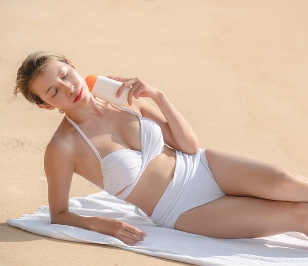 Frau im weißen bikini mit sonnencremeflasche in der hand am strand liegend.