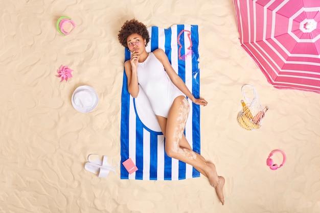 Frau im weißen bikini posiert auf handtuch am sandstrand verwendet sonnenschirm, um sich vor der sonne zu verstecken, fühlt sich unglücklich, weil sonnenbrand sonnencreme auf das gesicht aufträgt. sommerlebensstil