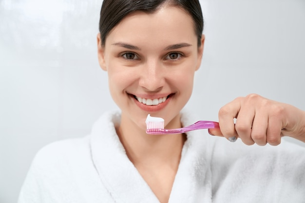 Frau im weißen gewand nach der dusche, die zahnbürste hält