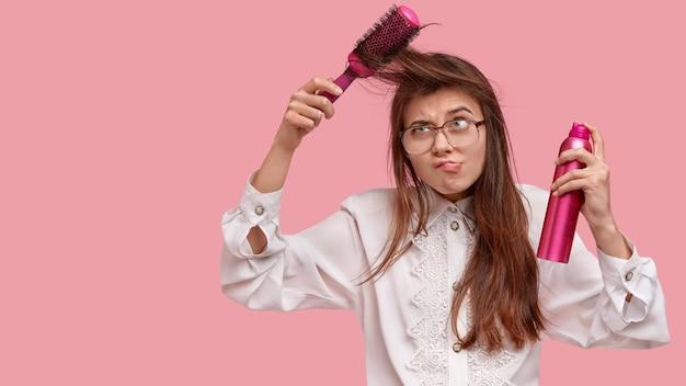 Frau im weißen hemd, das ihr haar stylt