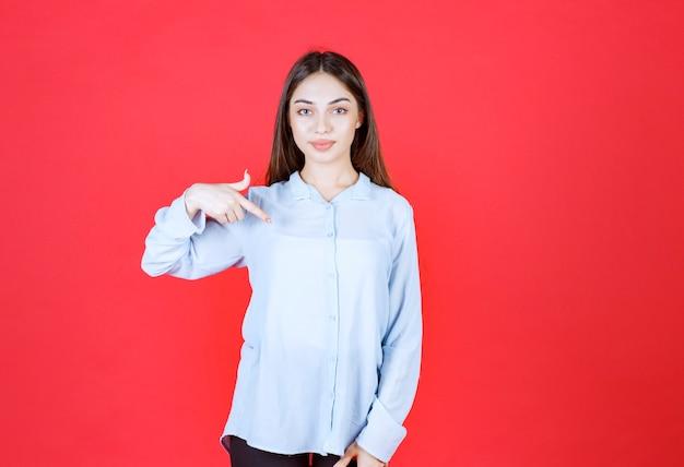 Frau im weißen hemd, die auf roter wand steht und auf sich selbst zeigt.