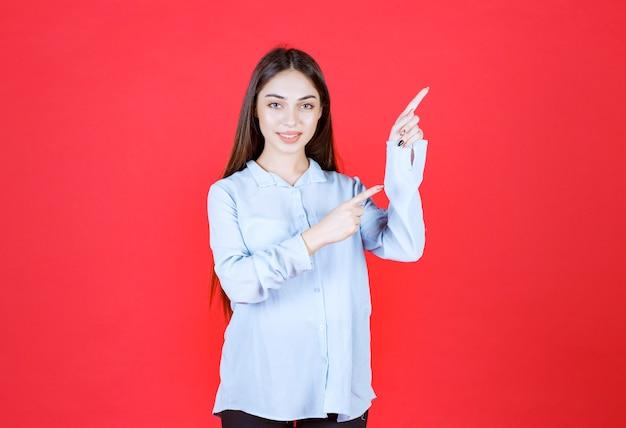 Frau im weißen hemd, die auf roter wand steht und rechte seite zeigt.
