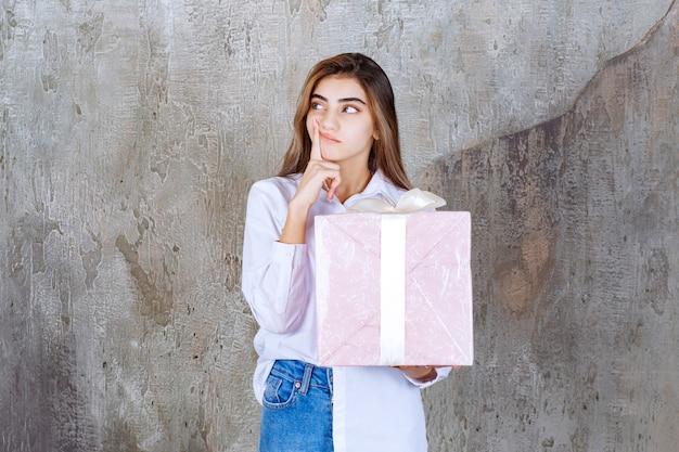 Frau im weißen hemd, die eine rosa geschenkbox hält, die mit weißem band eingewickelt wird und verwirrt und zögernd aussieht.