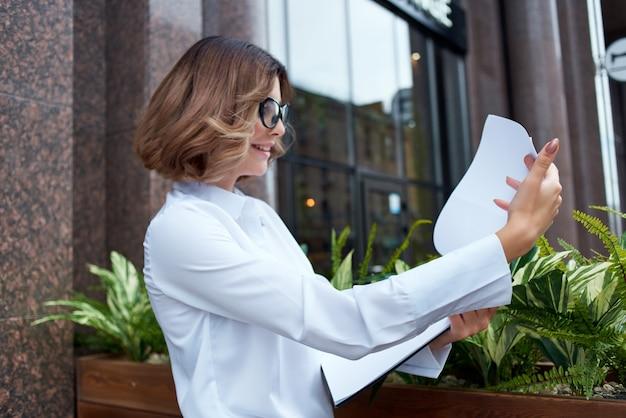Frau im weißen hemd managerdokumente auf der straße. foto in hoher qualität