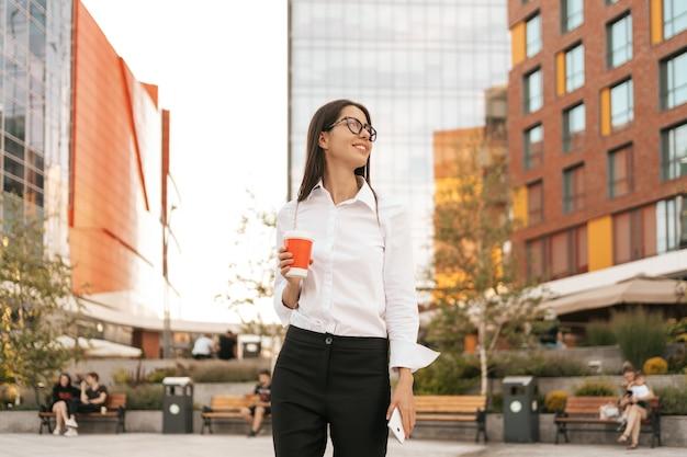 Frau im weißen hemd mit einem kaffee zum mitnehmen