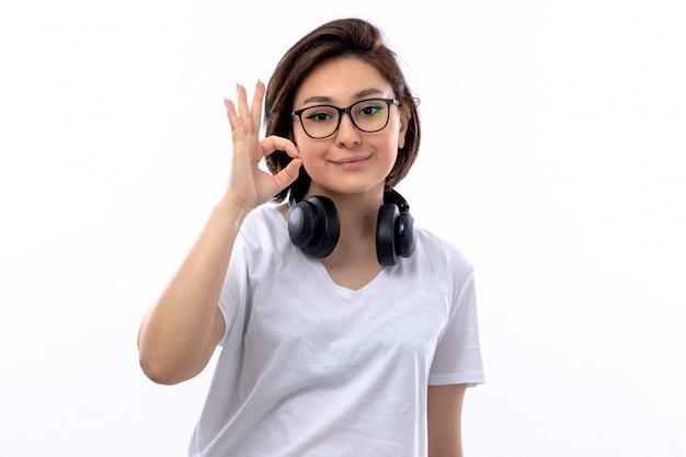 Frau im weißen hemd und in den schwarzen kopfhörern, die ok zeichen tun