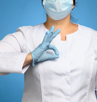 Frau im weißen kittel, blaue medizinische latexhandschuhe auf ihren händen tragend, zeigend ok geste, genehmigungskonzept