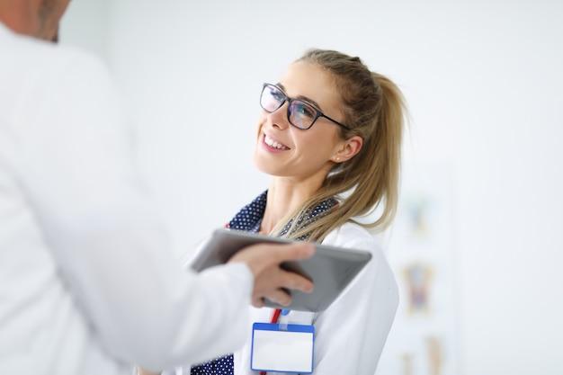 Frau im weißen kittel lächelt und kommuniziert mit einem angestellten, der tablette in seinen händen hält.