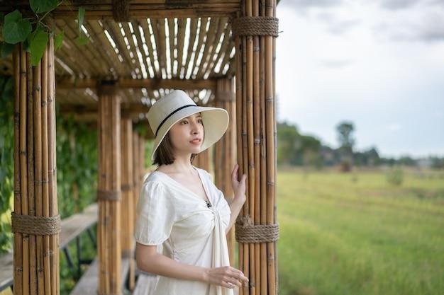 Frau im weißen kleid, das auf bambustunnel und brücke als weg durch das reisfeld geht.