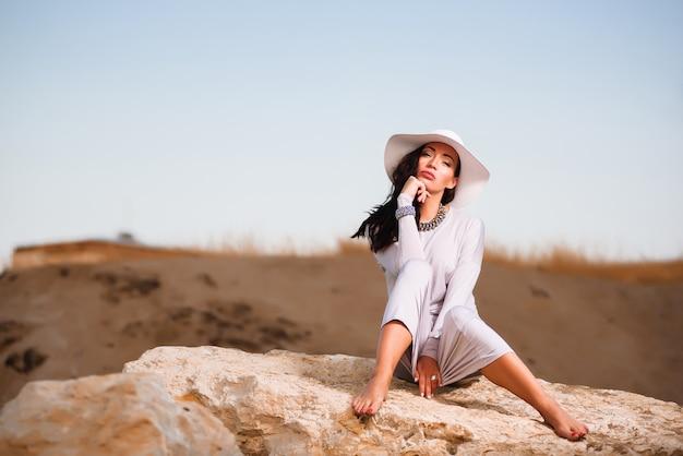 Frau im weißen kleid, das auf einem felsen am strand sitzt und weißen hut hält.